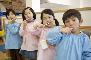 並んで歯を磨く幼稚園児4人