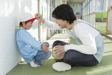 男の子に話しかける幼稚園教諭