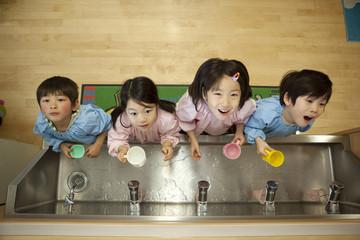 並んでうがいをする幼稚園児4人