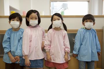 マスクを着けて並ぶ幼稚園児4人