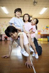 幼稚園教諭に馬乗りになる幼稚園児3人