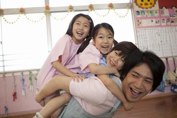 子供3人を背負う幼稚園教諭