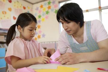 女の子に折り紙を教える幼稚園教諭