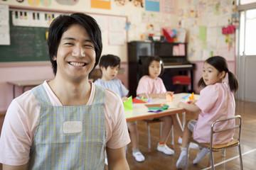 教室で笑う幼稚園教諭