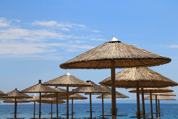Sunny beach with wicker umbrellas and blue sky