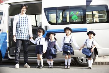 バスの前に並んで立つ幼稚園児と幼稚園教諭