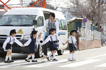 バスの前を並んで歩く幼稚園児と幼稚園教諭