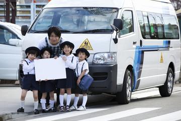 バスの前でホワイトボードを持つ幼稚園児と幼稚園教諭