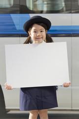 バスの前でホワイトボードを持った幼稚園の女の子
