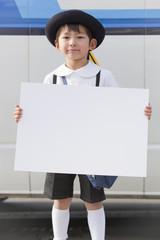バスの前でホワイトボードを持った幼稚園の男の子