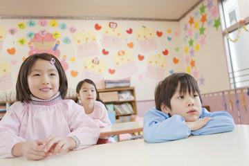 机に座った幼稚園児3人