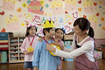 お誕生日会を行う幼稚園児と幼稚園教諭