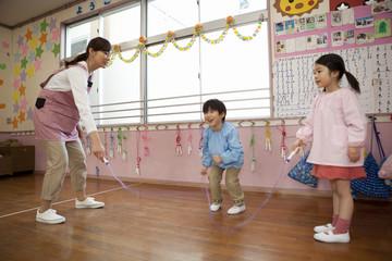 室内でなわとびをする幼稚園児と幼稚園教諭