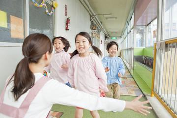 幼稚園教諭の元に駆け寄る幼稚園児