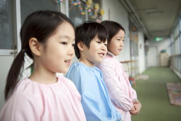 廊下に並んで立つ幼稚園児3人