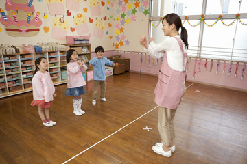 教室でお遊戯をする幼稚園児と幼稚園教諭