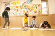 教室でお絵描きをする子供3人と保育士