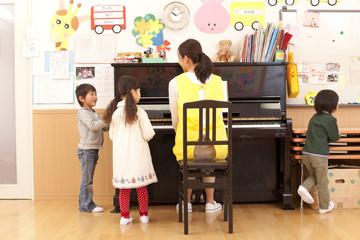 ピアノで遊ぶ子供3人と保育士