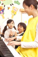ピアノで遊ぶ子供2人と保育士