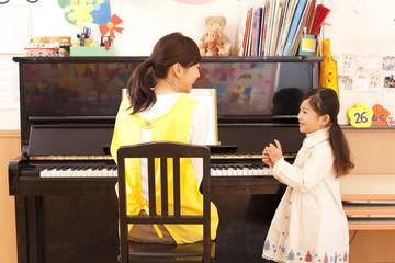 ピアノを弾く保育士と女の子