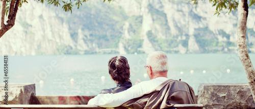 canvas print picture Älteres Paar sitzt gemütlich am See