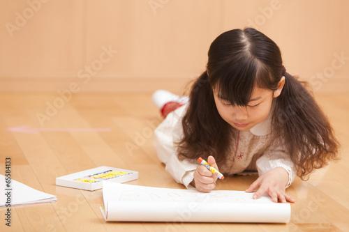 床に寝そべってお絵描きをする女の子