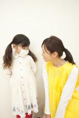 マスクを着けた女の子と保育士