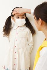女の子の熱を測る保育士