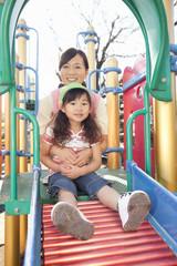 遊具で遊ぶ女の子と保育士