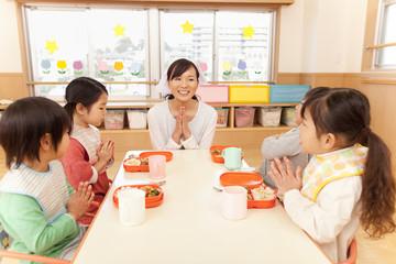 食事の挨拶をする子供4人と保育士