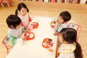給食を食べる子供4人