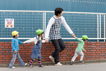 外を散歩する子供3人と保育士