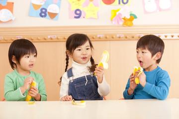 バナナを食べる男の子2人と女の子