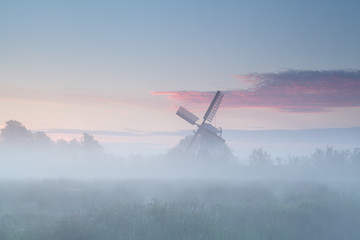 windmill in dense morning fog