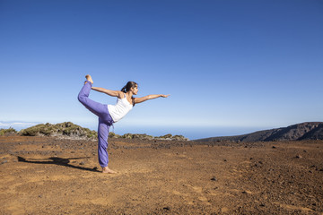 Young attractive woman doing dancers yoga pose outdoors on a des