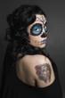 Junge Frau mit Sugar Skull Make up und Tattoo