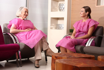 Two mature women patient talking in the hospital waiting room