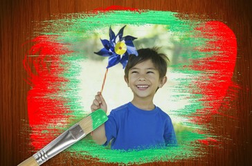 Composite image of little boy with pinwheel