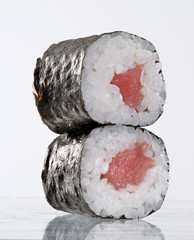 Dos sushi roll de atún en fondo blanco.