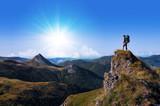 hiker on top of a rock looking far away - 65596960