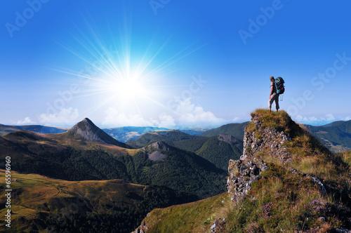 Leinwanddruck Bild hiker on top of a rock looking far away