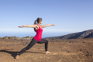 Young woman practicing yoga warrior pose on a desert mountain
