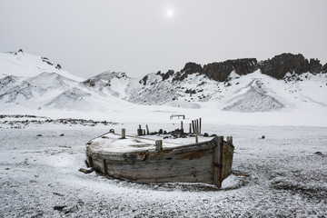 A wooden boat hull beached on Deception island, a former whaling station.
