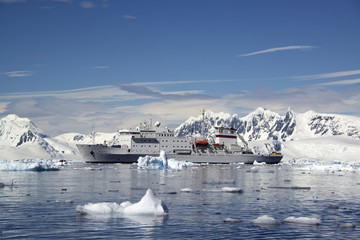 An Antarctic cruise ship with inflatable zodiacs on the calm waters among ice floes and mountainous landscape.