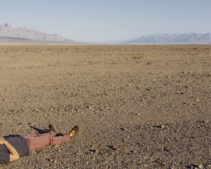 A man lying on his back on the ground in the desert.