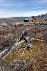 Broken fencing on grassland, and a barn in the open in the Green River lakes area.