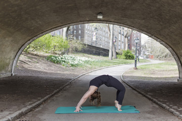 A young woman in Central Park, in a black leotard and leggings, doing yoga.