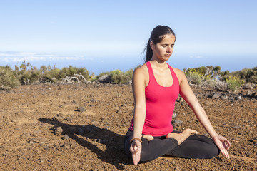 young woman practicing yoga meditation outdoors