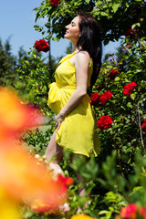 Pregnant woman resting in park with roses