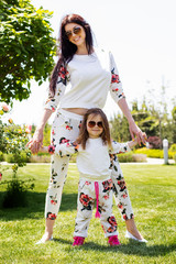 Beautiful mother and daughter relaxing on grass